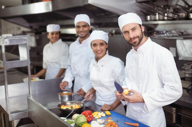 Chefs cortando vegetais na tábua da cozinha comercial