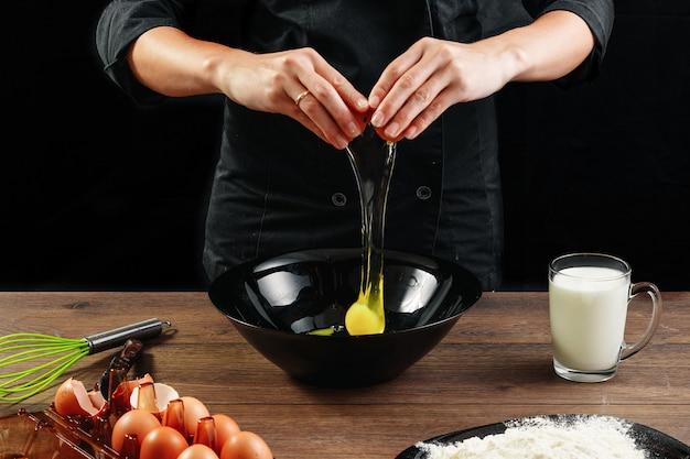Chefs de chef de mãos masculinas quebram o ovo em uma mesa de madeira marrom em uma tigela preta