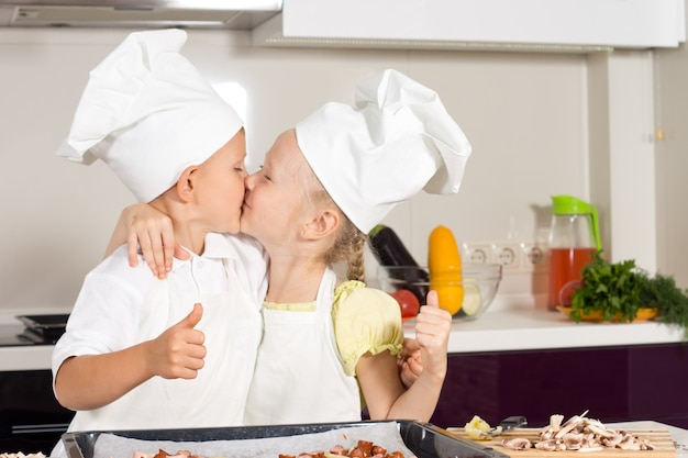Chefs de criança bonitinho beijando na cozinha para o sucesso do cozimento.