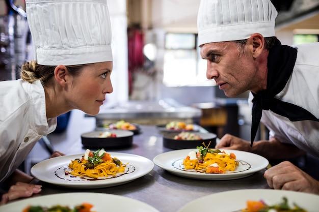 Chefs masculinos e femininos, olhando um ao outro na cozinha