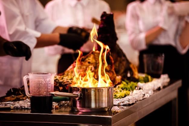 Chefs preparam comida em uma frigideira com fogo