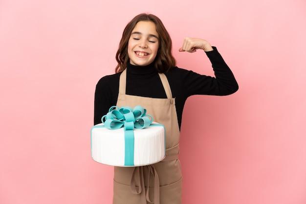 Chefzinho de confeitaria segurando um grande bolo isolado em um fundo rosa fazendo um gesto forte