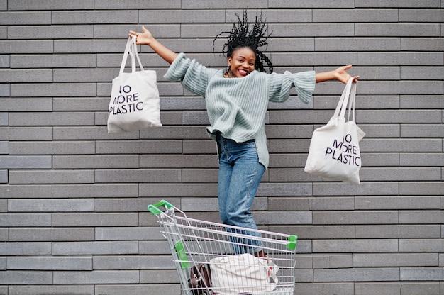 Chega de plástico. a mulher africana com sacos de carrinho e eco de carrinho de compras salta no mercado ao ar livre.
