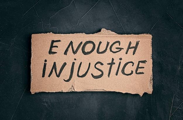 Chega de texto de injustiça em papelão sobre fundo escuro