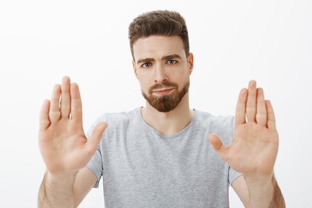 Chega eu farto. retrato de homem caucasiano bonito e masculino pressionado e descontente com barba e olhos azuis levantando as palmas das mãos em gesto de pare, sorrindo de não gostar de recusar sobre parede cinza