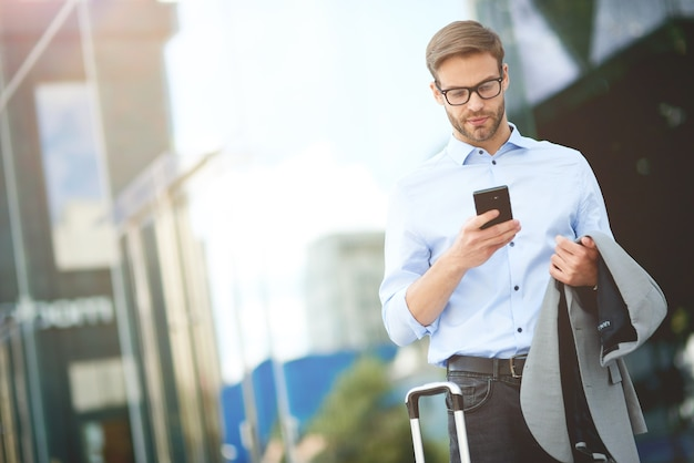 Chegando ao aeroporto jovem empresário bonito com mala usando smartphone enquanto espera por