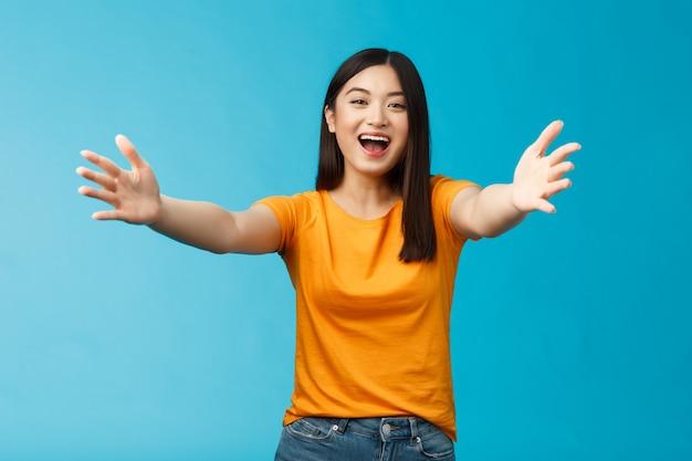 Chegue mais perto, deixe-me te abraçar. alegre linda menina morena asiática esticar as mãos para a frente quer abraçar, abraçando amigo sorrindo amplamente convidando queridos convidados boas-vindas, ficar de fundo azul.