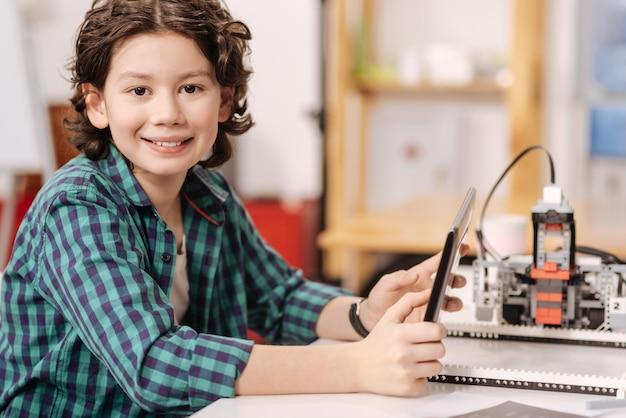 Cheio de alegria. garoto animado encantado sincero sentado na sala de aula e usando o tablet enquanto estuda e expressa positividade