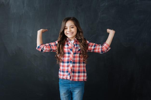 Cheio de alegria . linda garota feliz e sorridente em pé contra o quadro-negro e apreciando o desenho imaginário enquanto expressa felicidade