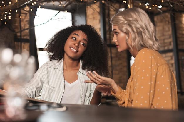 Cheio de ceticismo. mulher bonita e encaracolada sentada no balcão do bar com a amiga e ouvindo sua história com ceticismo