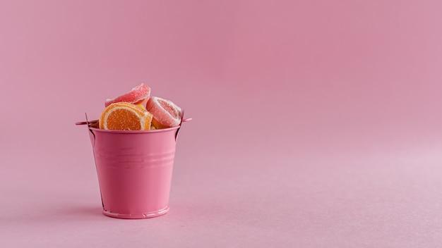 Cheio de doces de geléia de frutas coloridas em um balde rosa