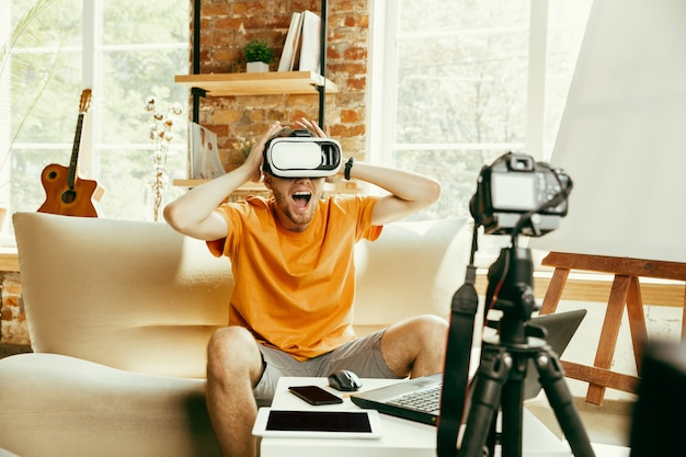 Cheio de emoções. blogueiro do sexo masculino, caucasiano, com câmera profissional, gravação de revisão de vídeo de óculos de vr em casa. blogging, videoblog, vlogging. homem usando fone de ouvido de realidade virtual durante a transmissão ao vivo.