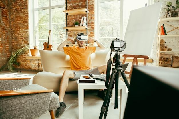 Cheio de emoções. blogueiro do sexo masculino, caucasiano, com câmera profissional, gravação de revisão de vídeo de óculos vr em casa. blogging, videoblog, vlogging. homem usando fone de ouvido de realidade virtual durante a transmissão ao vivo.