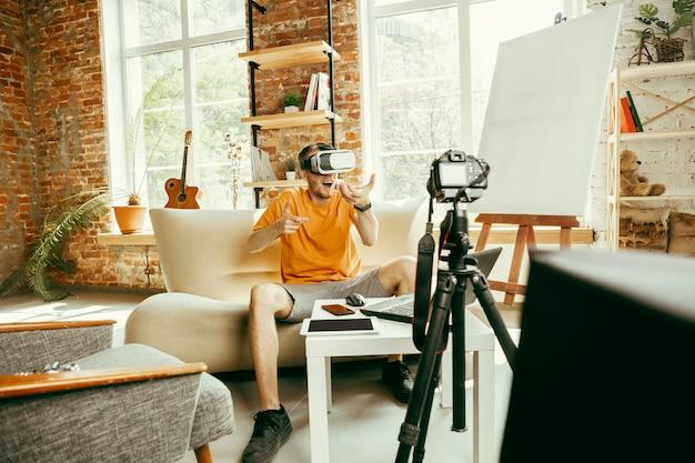 Cheio de emoções. blogueiro do sexo masculino, caucasiano, com câmera profissional gravando análise de vídeo de óculos de realidade virtual