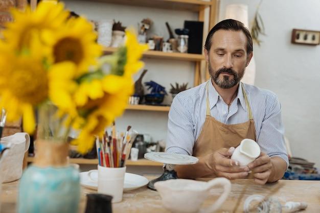 Cheio de girassóis. artesão sentindo-se alegre sentado à mesa com um vaso cheio de girassóis