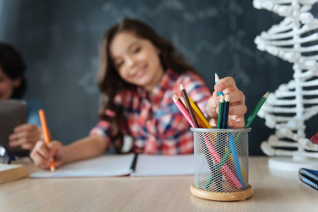 Cheio de ideias criativas. garota talentosa e artística sentada na escola, desenhando enquanto trabalhava no projeto e usando lápis coloridos