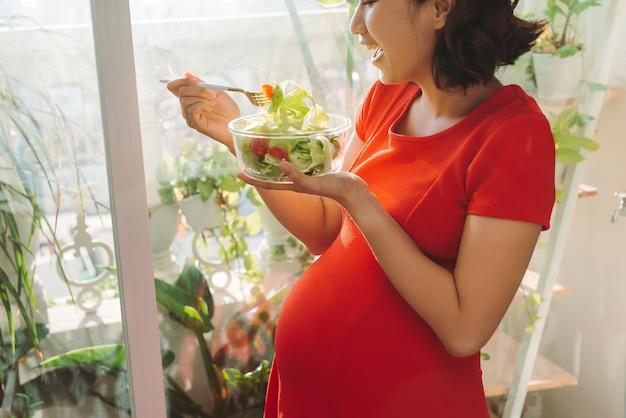 Cheio de vitaminas. mulher grávida de boa aparência enérgica comendo carne enquanto carrega o prato na mão e relaxa contra a janela