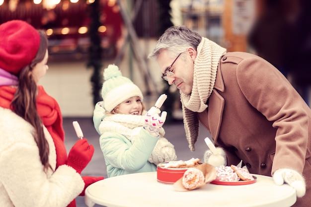 Cheio. garota atraente com um sorriso no rosto enquanto segura um doce na mão direita