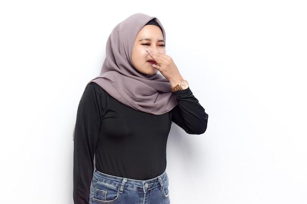 Cheirando algo fedorento e nojento de jovens lindas mulheres muçulmanas asiáticas