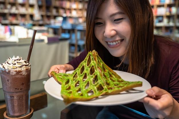 Cheiro de mulher asiática e olhar para o waffle antes de comer com bebida na mesa no coff moderno