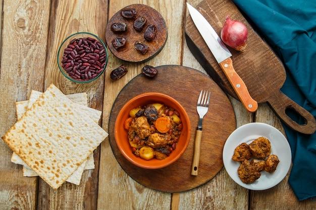 Chelnt de prato judeu com carne em um prato sobre uma mesa de madeira em um carrinho ao lado de uma faca e ingredientes. foto horizontal