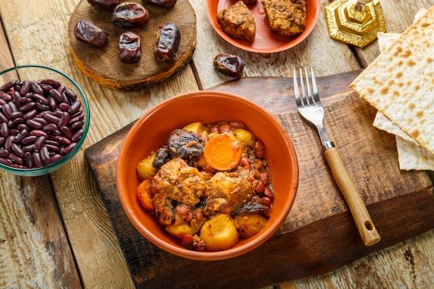 Chelnt de prato judeu com carne em uma barraca ao lado de pão ázimo e ingredientes.