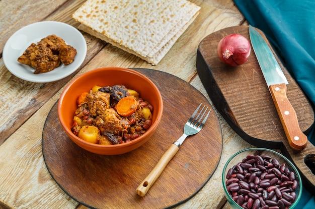 Chelnt de prato judeu com carne na mesa em um prato em um suporte ao lado dos ingredientes e pão ázimo. foto horizontal