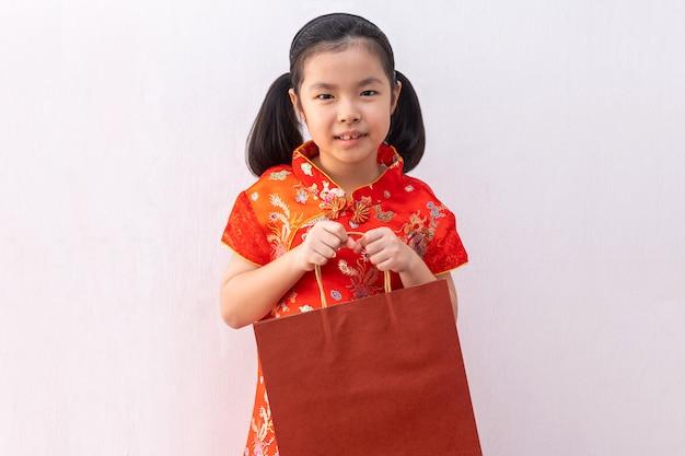 Cheongsam de desgaste de menina asiática segurar o saco de papel comercial.