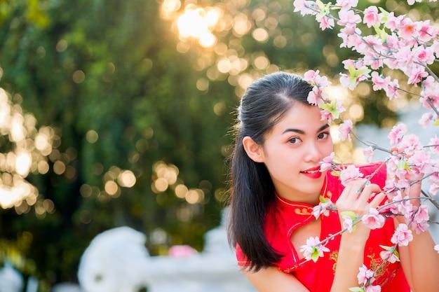 Cheongsam tradicional do vestido vermelho chinês da mulher do retrato no templo chinês.