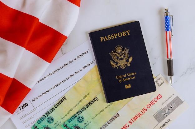 Cheque de alívio de estímulo passaporte dos eua na bandeira americana sobre o formulário 7200, pagamento antecipado de créditos do empregador devido ao covid-19