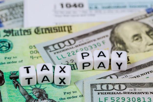 Cheque de retorno de imposto de estímulo econômico e 1040 formam imposto de renda individual com notas de dólar
