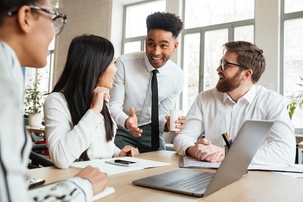 Cherful colegas jovens positivos usando computador portátil.