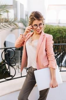 Cherful jovem busines mulher, estudante com laptop na mão, em pé na bela varanda, terraço em hotel, restaurante, resort. usando óculos da moda, jaqueta rosa, blusa bege, calça cinza.