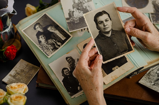 Cherkasy / ucrânia - 12 de dezembro de 2019: mãos femininas segurando e foto antiga de sua mãe. álbum de fotos vintage com fotos. conceito de valores de família e vida.