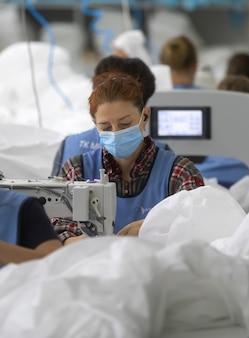 Chernigiv, ucrânia - 06 de outubro de 2020: costura de roupas de proteção para médicos e médicos durante a pandemia covid-19 na fábrica de costura tk-style em chernigiv, ucrânia