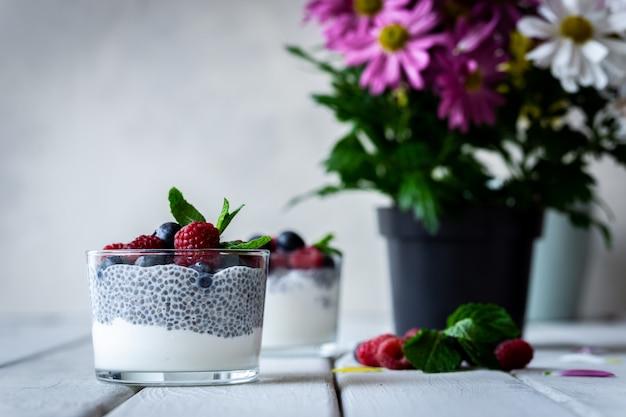 Chia com frutos silvestres. framboesas e mirtilos. sobremesa deliciosa e saudável e flores violetas sobre uma mesa rústica de madeira branca.