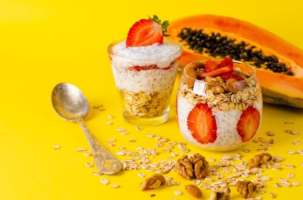 Chia pudim de iogurte com morangos, farinha de aveia e nozes em um copo amarelo