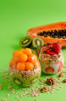 Chia pudins com frutas tropicais frescas crus com aveia e nozes para uma alimentação saudável em verde