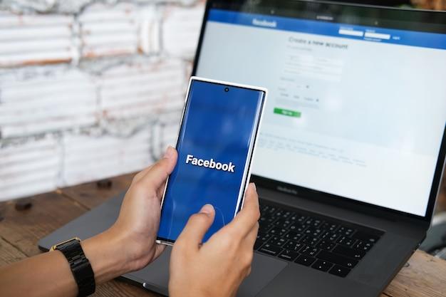 Chiang mai, tailândia. 06 de junho de 2021. mulher segura smartphone com aplicativo do facebook na tela. facebook é um aplicativo de compartilhamento de fotos para smartphones.