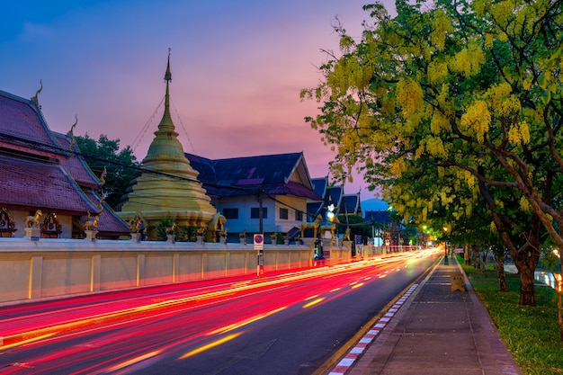Chiang mai, tailândia - abril de 10,2020: árvore de fístula amarela de cassia com trilhas leves na rua em wat wat khwr kha ma é uma antiga muralha e fosso da cidade velha de templo budista
