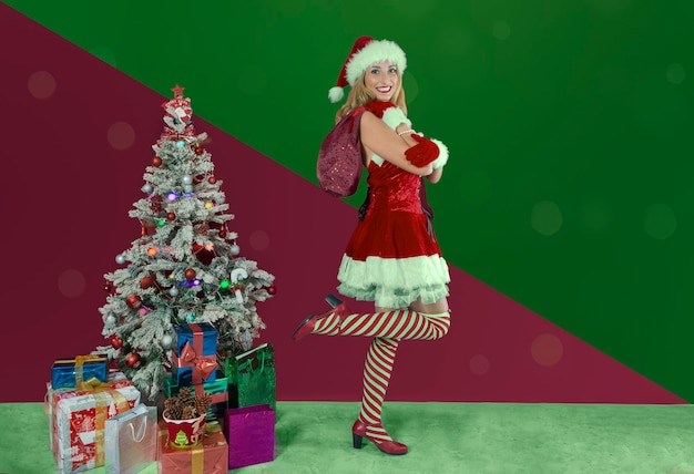 Chica en vestido de papai noel de torta com uma pierna delante de um fundo de cores