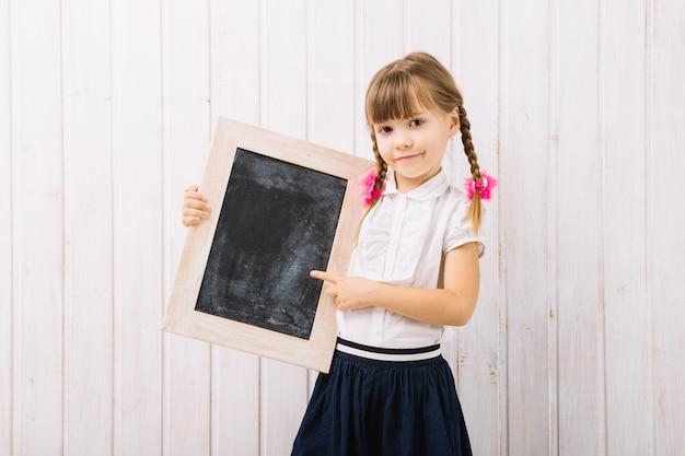 Chica encantadora apontando para quadro-negro