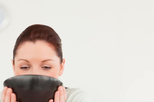 Chica encantadora bebendo uma tigela de café