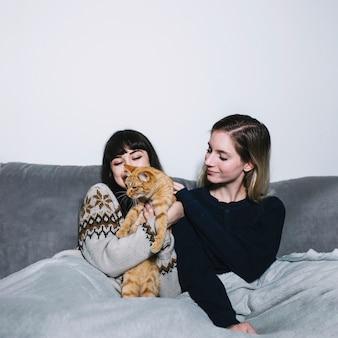 Chicas encantadoras abraçando com gato no sofá