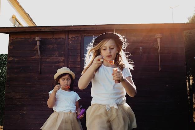 Chicas encantadoras em chapéus que sopram bolhas