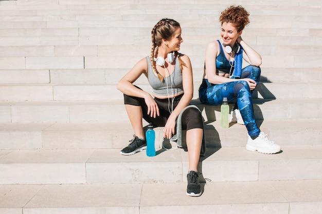 Chicas encantadoras em roupas esportivas nos degraus