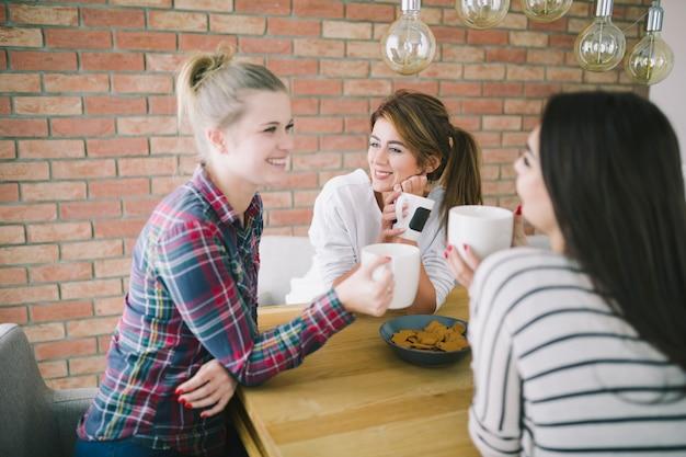 Chicas encantadoras que gostam de chá na cozinha