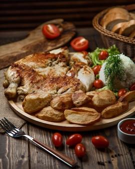 Chicke grelhado e batatas com arroz, frutas, endro e tomate.