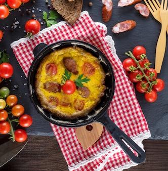 Chicoteado ovos fritos em uma frigideira preta redonda
