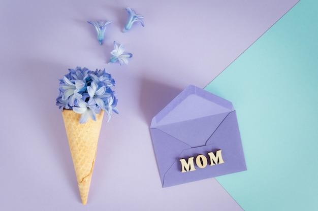 Chifre ou cone do gelado com jacinto roxo em um roxo - fundo da hortelã.
